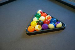 Pool billiard balls in a wooden rack on black background stock images