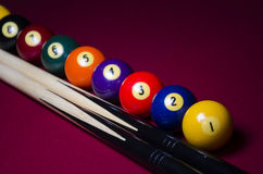 Pool Billiard line up. An artistic dramatic shot of a Red Felt Pool Table with Pool sticks and the vintage old balls as the first three balls on the right as the stock photo