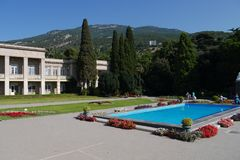 Pool with blue water and flower beds on the sides near a beautiful building against the background of green mountains royalty free stock images