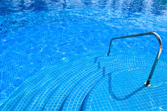 Pool with blue water stairs rail at daylight Royalty Free Stock Photo