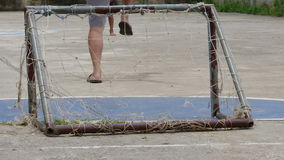Pool boy kicking old football have laceration and net laceration small goal. Pool boy kicking old football have laceration and net laceration small goal with stock video