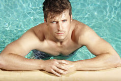 Pool boy. Summer portrait of a handsome young cool guy in the pool Royalty Free Stock Photos