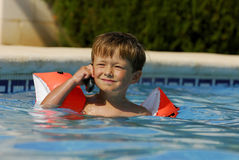 Pool Phone Call. Boy child makes a call with a cell-phone in a swimming-pool stock images