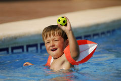Pool business 11. Boy child is playing with a ball in a swimming-pool royalty free stock photo