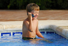 Pool Phone Call. Boy child makes a call with a cell-phone sitting in a swimming-pool stock photos
