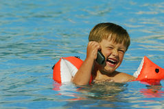Pool Phone Call. Boy child makes a call with a cell-phone in a swimming-pool royalty free stock image