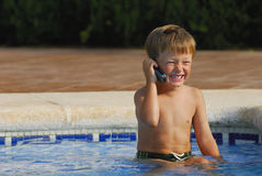 Pool Phone Call. Boy child makes a call with a cell-phone sitting and laughing in a swimming-pool stock photo