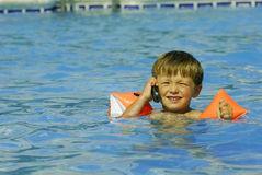 Pool business 3. Boy child makes a call with a cell-phone in a swimming-pool royalty free stock photos