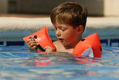 Boy in Pool with Cell Phone. Boy child makes a call with a cell-phone in a swimming-pool stock photo