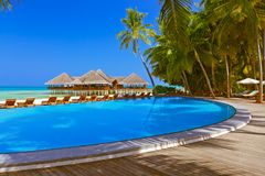 Pool and cafe on Maldives beach royalty free stock photography