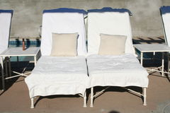 Pool chairs. Set up with pillows and suntan oil Stock Image