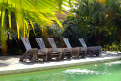 Pool chairs on deck at a hotel in tropics Stock Images