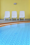 Pool Chairs empty in hotel on caribbean sea. Spa resort lounge chairs in relaxing environment Stock Image