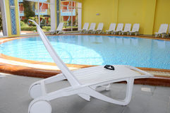 Pool Chairs indoor. View from window on pool and flowerses Royalty Free Stock Photography