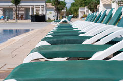 Pool and chaise longues. Blue swimming pool and chaise longues, summer royalty free stock photos