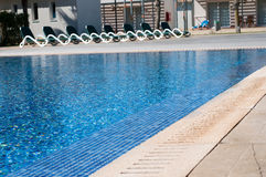 Pool and chaise longues. Blue swimming pool and chaise longues, summer stock photography