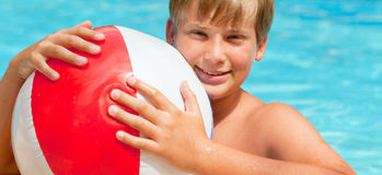 Pool child. Boy with water ball in swimming-pool smiling stock images