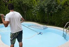Pool cleaner. A pool cleaner boy is on the work Stock Images