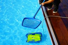 Hotel staff worker cleaning the pool. Automatic pool cleaners. royalty free stock images