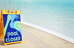 Pool Closed Sign. Tropical pool closed sign next to empty pool Stock Images