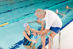 Pool coach - swimmer training competition. Swimming pool - swimmer training competition in class with coach Stock Photography