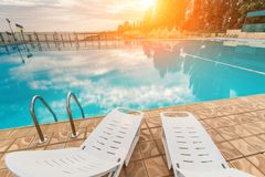 Pool and a couple of sun loungers. Pool with clear, clean water and a couple of sun loungers around it stock photography