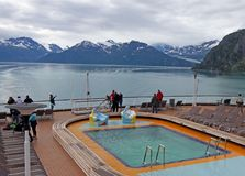 Pool On A Cruise Ship. A small Pool on a cruise ship deck with people enjoying the beautiful view of Alaska`s mountains Royalty Free Stock Photo