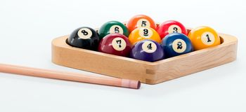 Pool cue and nine ball rack of balls ready for a billiards game. Pool game of balls and cue on a white background Royalty Free Stock Image