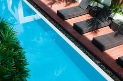 Pool with dark chairs beside Stock Photo