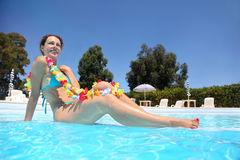 In pool in day-time woman sits in swimming suit Royalty Free Stock Photos