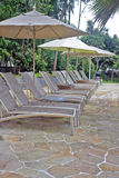Pool deck chairs. Deck chairs and umbrellas by the pool royalty free stock photography