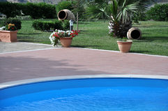 Pool deck in countryside. Pool deck in rural agriturismo location with swimming pool and garden Stock Photography