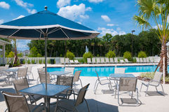 Pool Deck Umbrella chairs and tables on a sunny day Stock Image