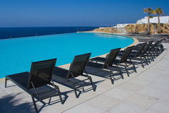Pool and deckchairs. An infinity pool and pool chairs Royalty Free Stock Images
