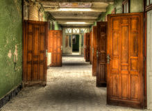 Pool Doors. An abandoned pool with a hallway full of doors to private rooms with baths and showers royalty free stock photo