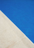 Pool edge. Enticing image of blue water and stone swimming pool edge Royalty Free Stock Photography