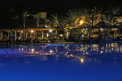 Pool and evening hotel on vacation. People relax in evening near pool royalty free stock photography