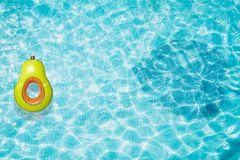 Pool float, ring floating in a refreshing blue swimming pool with palm tree leaf shadows in water Stock Photo