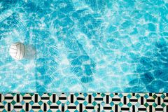 Pool float, ring floating in a refreshing blue swimming pool with palm tree leaf shadows in water Royalty Free Stock Photo