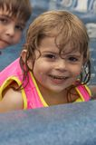 Pool fun. Young pretty girl smiling in water royalty free stock photos