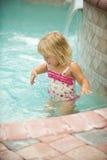 Pool Fun. Adorable little girl splashing in swimming pool Stock Photography