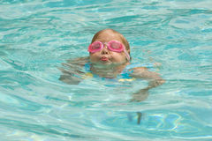 Pool Fun. Adorable little blond girl swimming in pool with pink goggles Stock Image