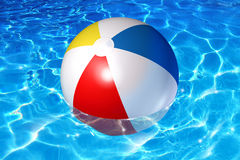 Pool Fun. Concept with an inflatable plastic beach ball floating in cool crystal clear reflective water as a symbol of vacation relaxation in a family backyard Royalty Free Stock Image