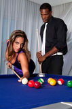 Pool game. Multiracial couple playing pool at night in upscale place Royalty Free Stock Photos