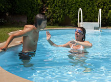 Pool games. A couple is joking each in the pool stock images