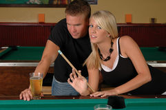 Pool Games. A young couple playing pool and drinking beer royalty free stock images