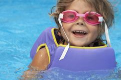 Pool goggles. A young girl playing in pool royalty free stock photography
