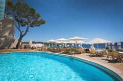 Pool at The Grand Tortuga restaurant. CALA FORNELLS, MALLORCA, SPAIN - SEPTEMBER 6, 2016: Pool at The Grand Tortuga restaurant with ocean view on a sunny day on Royalty Free Stock Image