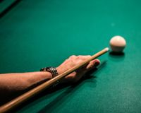 The Pool Hall. Hitting a cue ball at the pool table stock photo