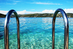 Pool handrails next to the sea. Going swimming. Cristal clear water Stock Photos